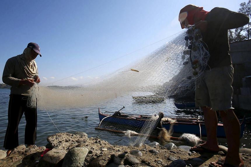 Fishermen sort their nets in the coastal town of Masinloc, Zambales, about 130 nautical miles from disputed Scarborough Shoal, in northern Philippines on April 22, 2015.