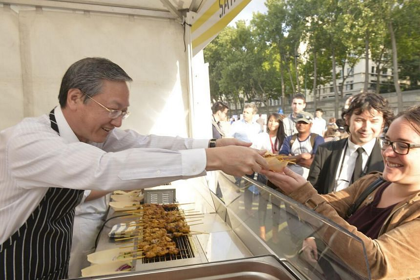 Minister of State in the Prime Minister's Office and in the Ministry of Culture, Community and Youth Mr Sam Tan (right) serving satay to visitors at the Saveurs de Singapour event.