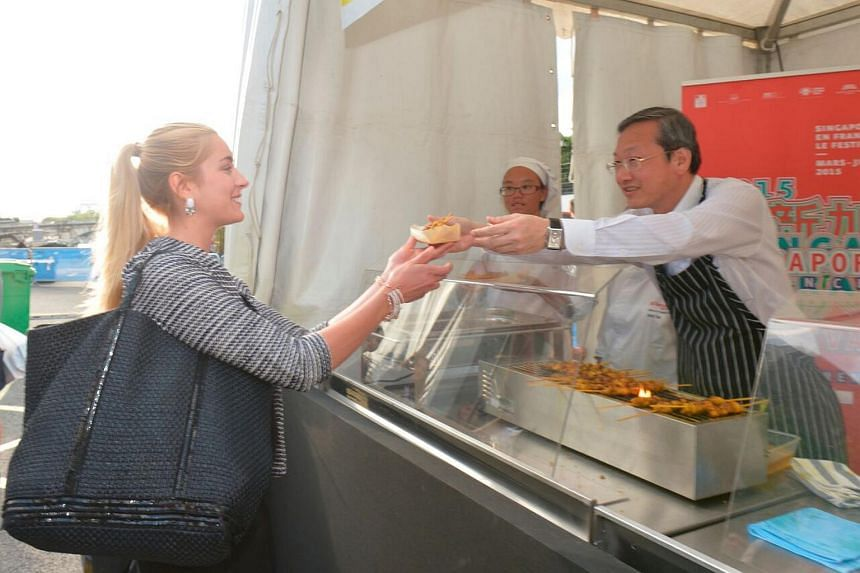 Minister of State in the Prime Minister's Office and in the Ministry of Culture, Community and Youth Mr Sam Tan (right) serving satay to a French visitor at the Saveurs de Singapour event along the banks of the River Seine in Paris, France.