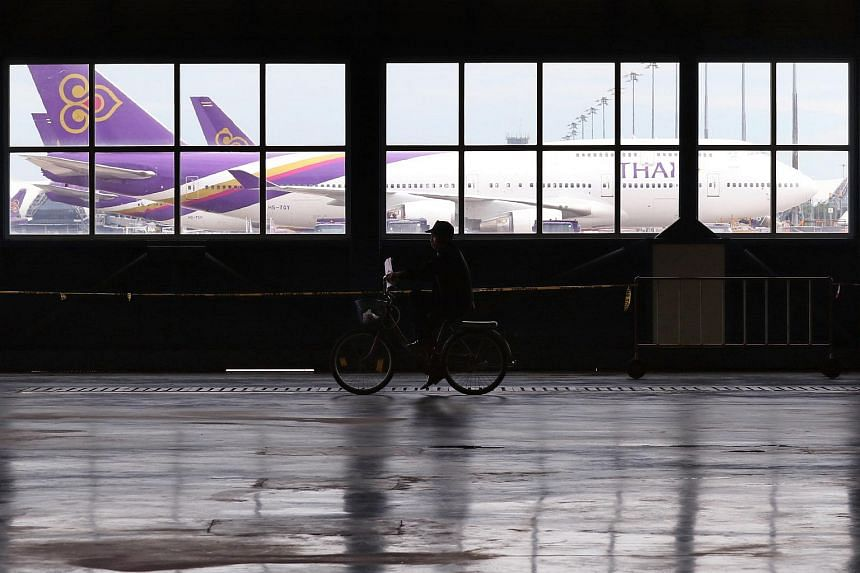 A security guard riding a bicycle inside the Technical Department of Thai Airways in Bangkok, Thailand.