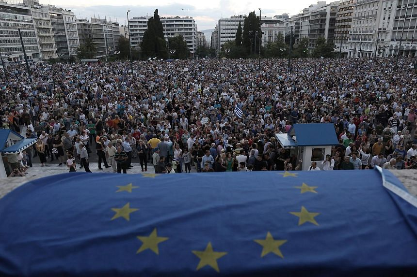 Demonstrators outside the parliament in Athens, Greece, take part in a rally demanding that Greece remains in the Eurozone on June 18, 2015.