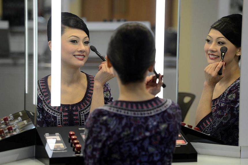 A Singapore Airlines in-flight supervisor applying her makeup at the SIA training centre.