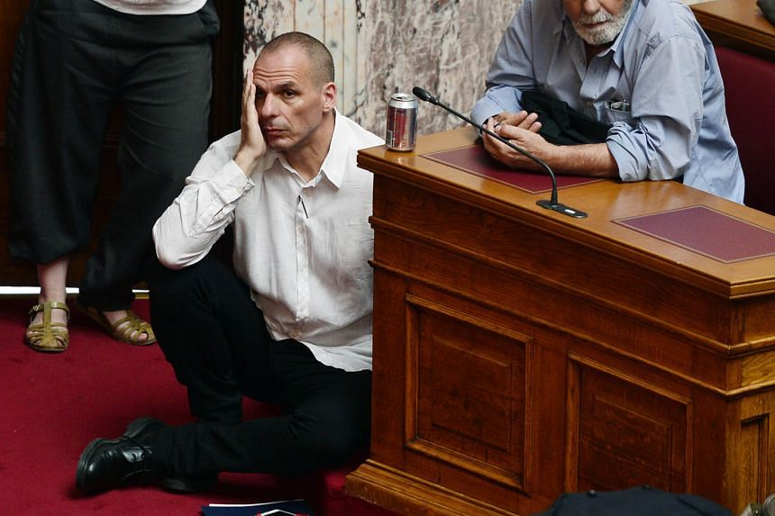 Greek Finance Minister Yanis Varoufakis (left) in a sombre mood as he listened to Prime Minister Alexis Tsipras addressing Parliament in Athens on Tuesday. Dr Varoufakis does not hold out much hope of a breakthrough at the euro zone finance ministers