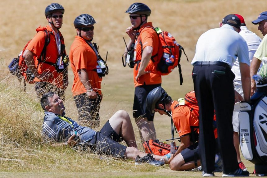 Emergency personnel attending to Stephen Gallacher's caddie Damien Moore after he twisted his ankle and injured himself in the rough on the sixth fairway during practice for the 115th US Open Championship at Chambers Bay.