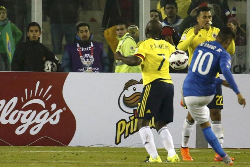 TROUBLE STARTS: Brazilian star Neymar fires a shot that hits Pablo Armero after the referee blows the final whistle.