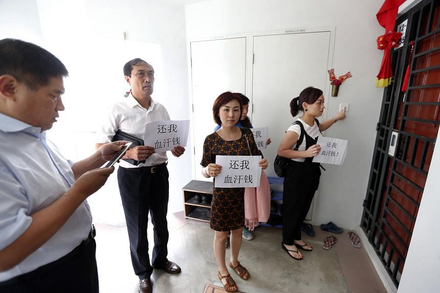 """The seven investors from China turned up at the flat of one of the alleged scammers, holding messages reading """"Return our hard-earned money""""."""