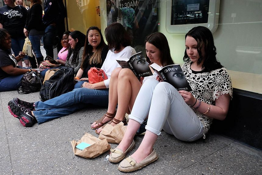 E.L. James' (left) new book, Grey, being read by fans outside a New York book store.