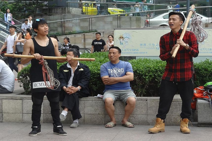 Wang Weiliang (above) and Tosh Zhang trying to barter objects they brought with them to China.