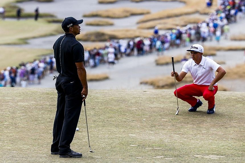 Tiger Woods (far left), having to settle for a bogey five on the fourth hole on Thursday. But he tried to make light of the situation by saying that his 80 score was still better than the 81 achieved by fellow American Rickie Fowler.