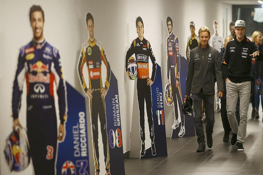 Mercedes' Nico Rosberg (left) with fellow German, Force India's Nico Huelkenberg, passing cardboard figures of drivers on their way to a news conference ahead of the Austrian Grand Prix.