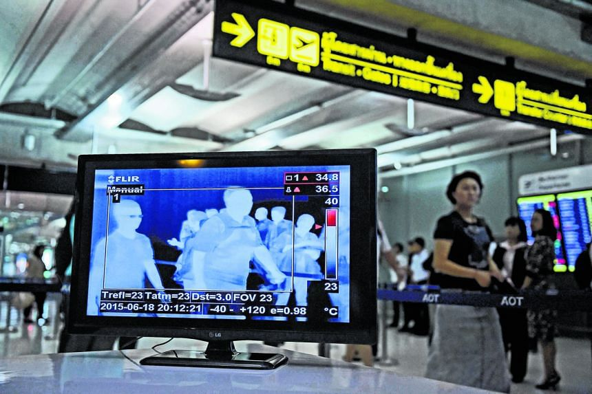 Travellers arriving at Bangkok's Suvarnabhumi Airport being scanned for fever (above), while (left) a woman dons a mask at Bamrasnaradura Infectious Diseases Institutewhere the Mers patient is being isolated.