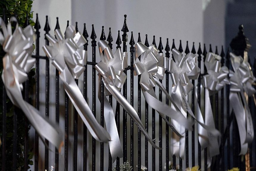 White ribbons commemorating victims of the hate crime on a railing outside the Emanuel African Methodist Episcopal Church in Charleston, South Carolina. Police leading suspected killer Dylann Roof into the courthouse in Shelby, North Carolina on Thur