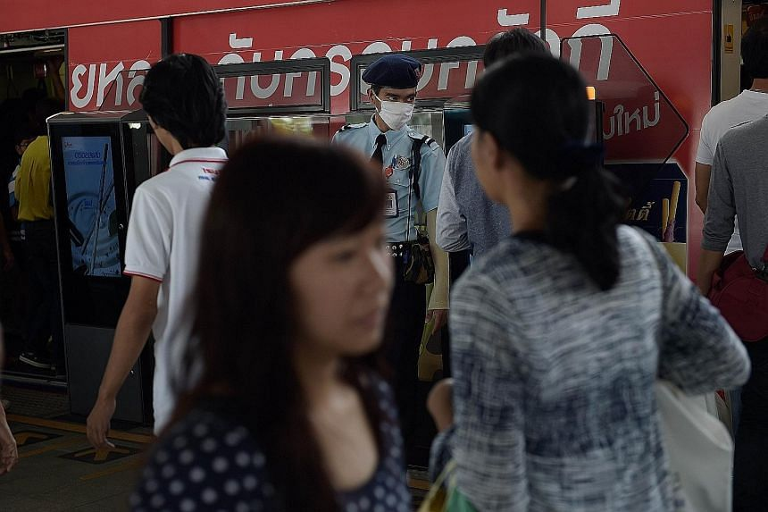 Commuters under the watchful eye of a security guard in a face mask at a Bangkok train station yesterday. Currently, 59 people are being monitored by the authorities for suspected Mers infection.