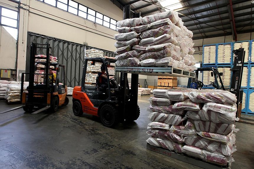 A worker stacking rice at a warehouse in Pasir Panjang. Major rice importers here, like NTUC FairPrice, stockpile at least three months' supply of rice to ensure they can cope with fluctuations in stock from overseas. Supermarket chains and rice impo