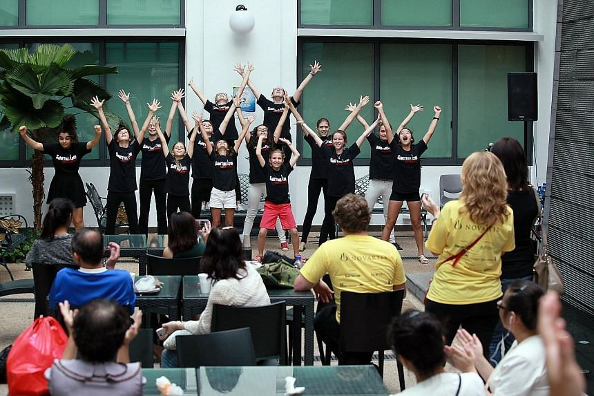Young members of the Sing'theatre Academy (above) putting up a song-and-dance performance yesterday. Meanwhile, patient Seah Mui Huay (below), 79, sang along as actor/DJ Hossan Leong Leong performed the Teresa Teng classic, The Moon Represents My Hea