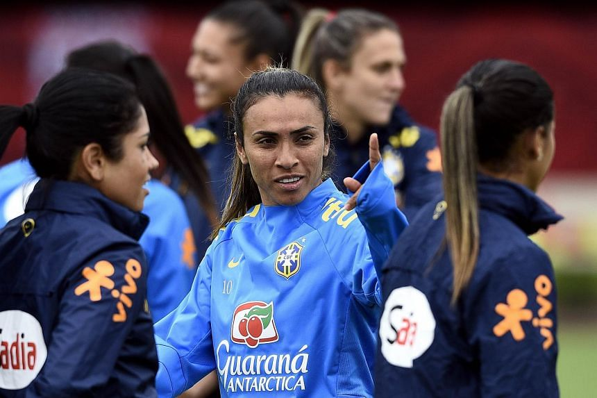 Brazil's midfielder Marta (centre) speaking with teammates during a training session in Moncton, New Brunswick.