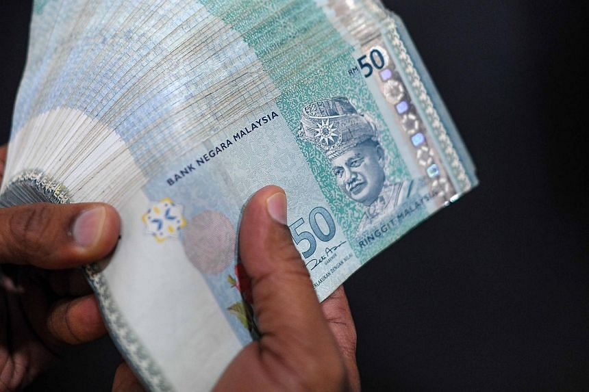 A money changer counting Malaysian ringgit banknotes.