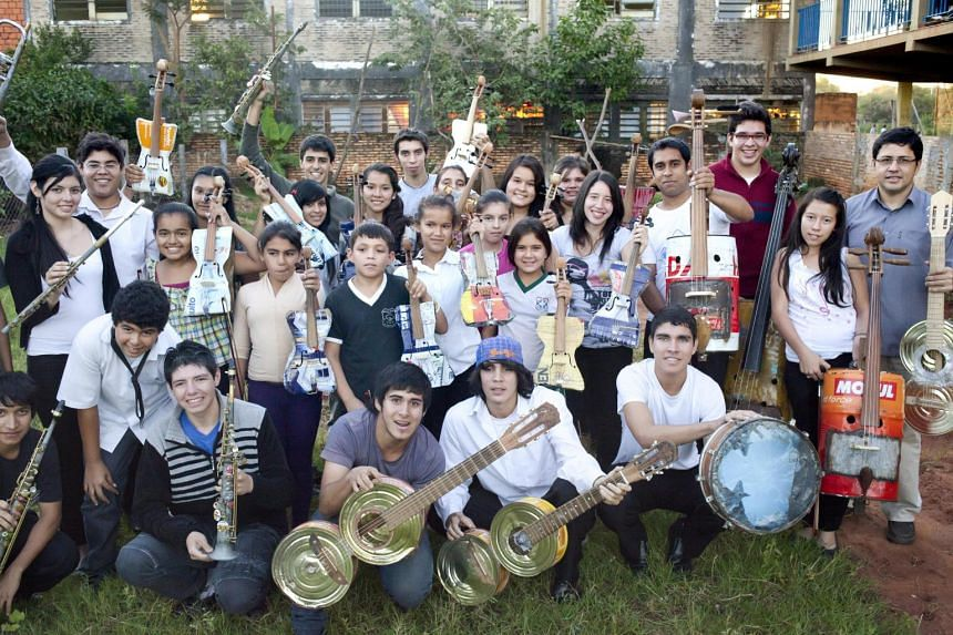 Members of the Orquesta de Instrumentos Reciclados de Cateura – or the Recycled Instruments Orchestra of Cateura – in front of their music school in Cateura, Paraguay. Thanks to donations, they now have conventional instruments they use in rehear