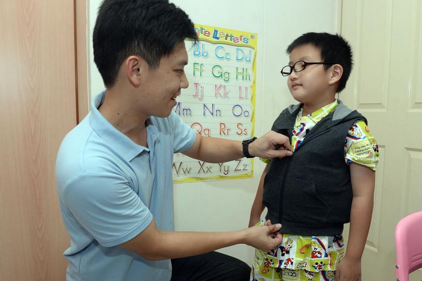 """Dr James Teh, 34, demonstrating the T.Jacket – a pressure vest that can remotely """"hug"""" people with special needs when they are feeling distressed to calm and console them. The jacket can also be activated by the wearer."""