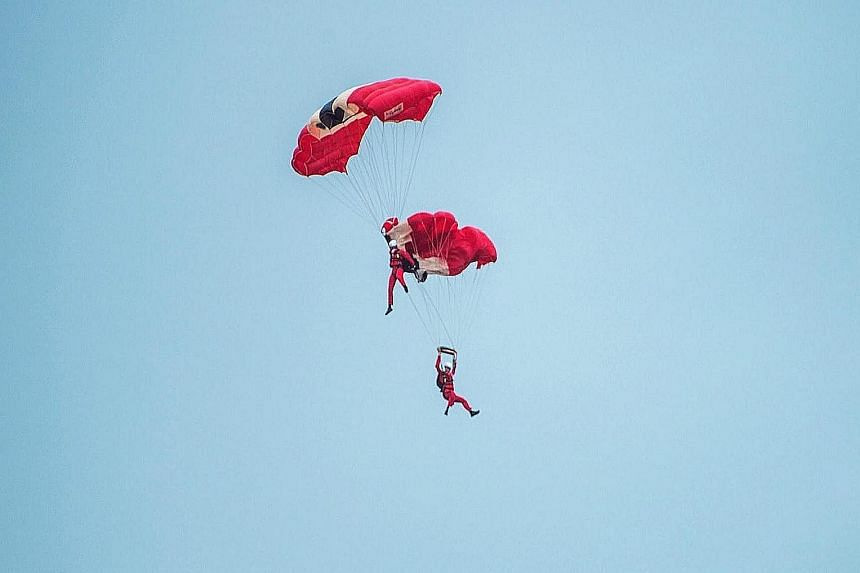 From far left: The teammate of the Red Devil parachutist, whose chute failed to open during the air show, grabs the tangled parachute, then manoeuvres their descent for a safe landing in the water at Queens Dock.