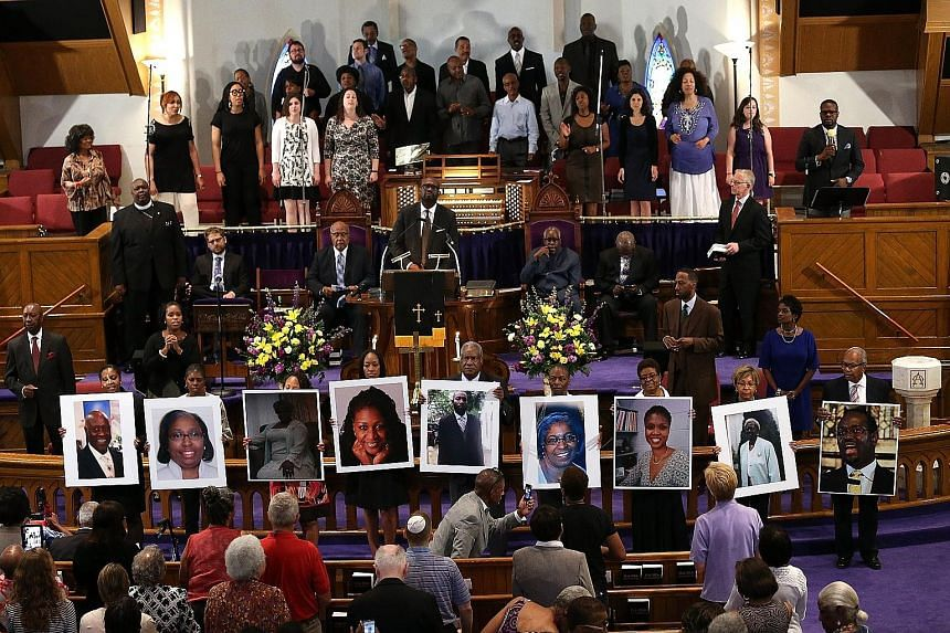 Photographs of the nine victims killed at the Emanuel African Methodist Episcopal Church in Charleston, South Carolina, are held up during a prayer vigil at the Metropolitan AME Church on Friday in Washington, DC.