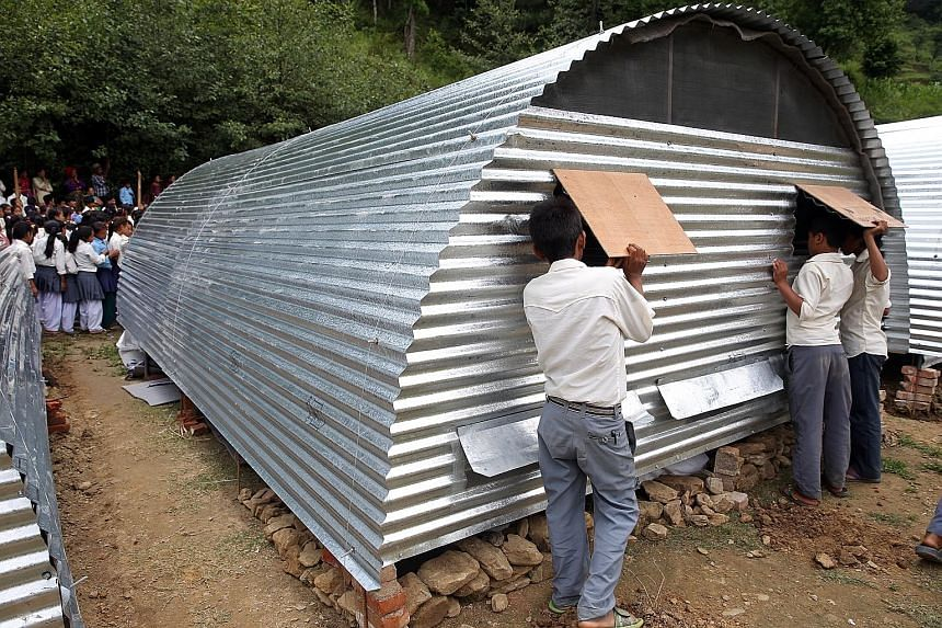 Mercy Relief is using $220,000 of Singapore public donations to build shelters (above) to withstand rain until October, when it can start work on permanent homes. For now, many quake survivors are housed in tents (below).