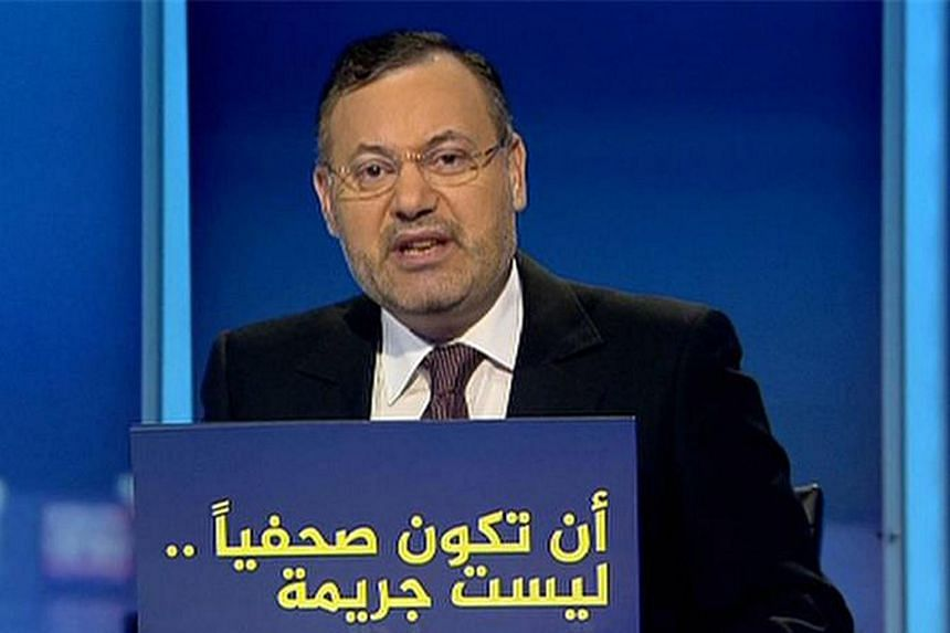 "Egyptian journalist and Al-Jazeera Arabic presenter Ahmed Mansour sitting behind a placard which reads in Arabic ""Journalism is not a crime"" at the network's studios in Doha."
