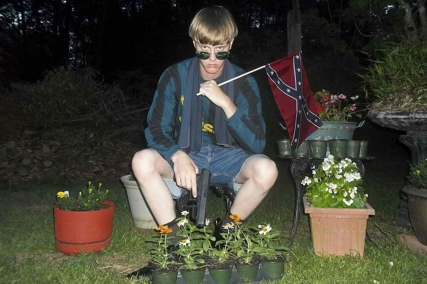 A photo from the alleged Dylann Roof website, with the suspected Charleston gunman holding a Confederate flag and a gun.