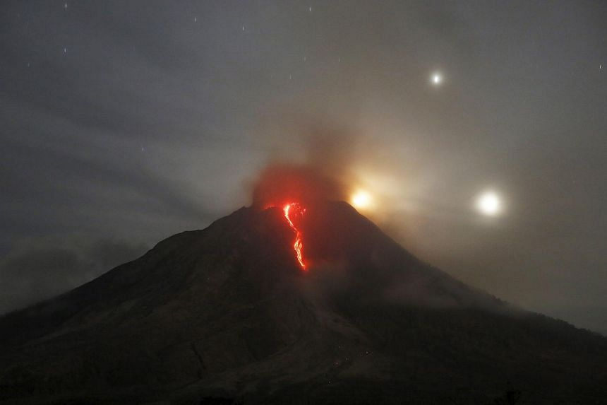 Ash spews from Mount Sinabung, as seen from Perteguhan village in Karo Regency, Indonesia's North Sumatra province, on June 20, 2015.