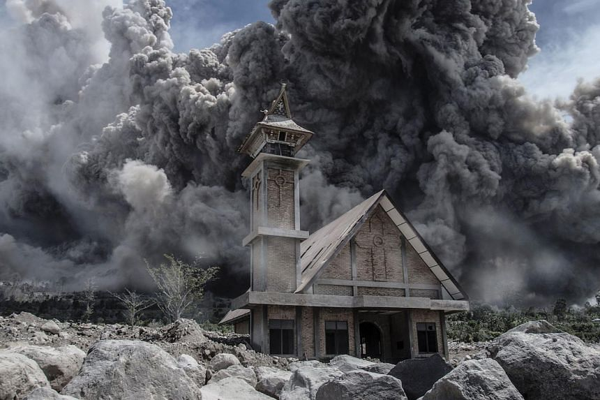 Mount Sinabung volcano fills the sky over an abandoned church during another eruption in Karo, Indonesia's North Sumatra province on June 19, 2015.