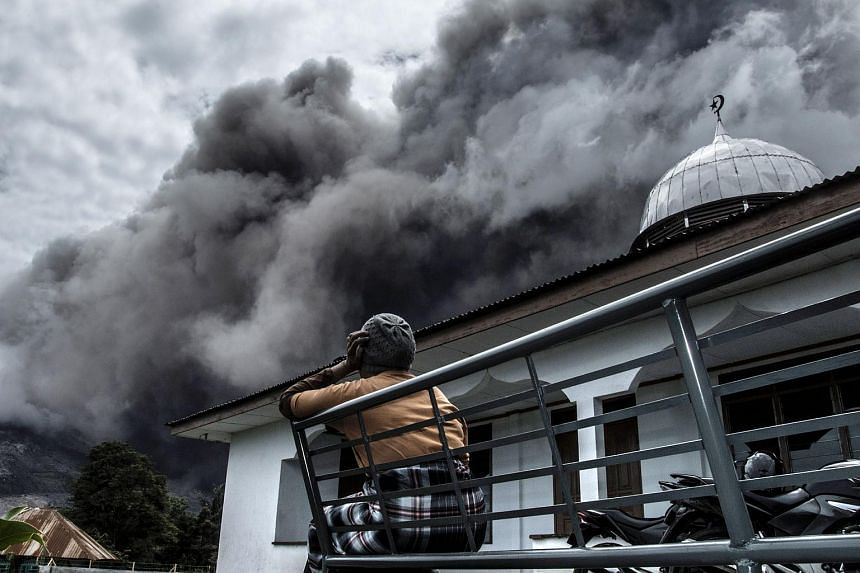 An Indonesian woman looks on as Mount Sinabung spews ash near a village in Karo district, North Sumatra province, on June 16, 2015.