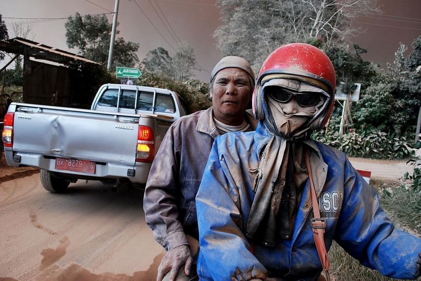 Residents with faces covered in ash ride on a motorcycle as Mount Sinabung volcano erupts, in Sukandebi village in Karo Regency, Indonesia's North Sumatra province, on June 13, 2015.