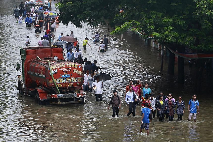 People walk through a flooded road as a water tanker is seen stuck due to heavy rains in Mumbai, India.
