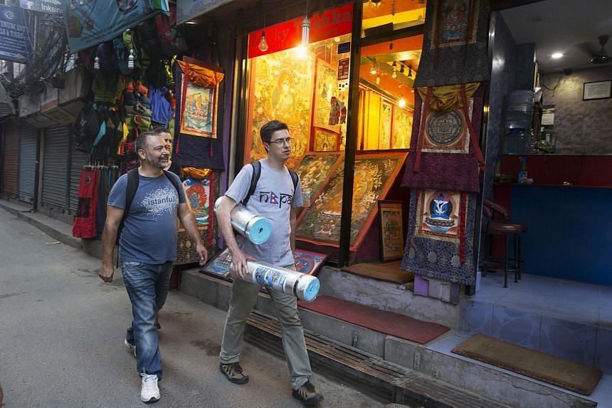 Men walk down a street in the Thamel area of Kathmandu, Nepal, on Friday, May 29, 2015.