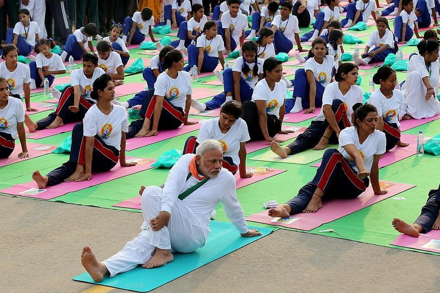 Indian prime minster Narendra Modi (centre) performs yoga to mark the first international Day of Yoga at Rajpath in New Delhi, India, on June 21, 2015.