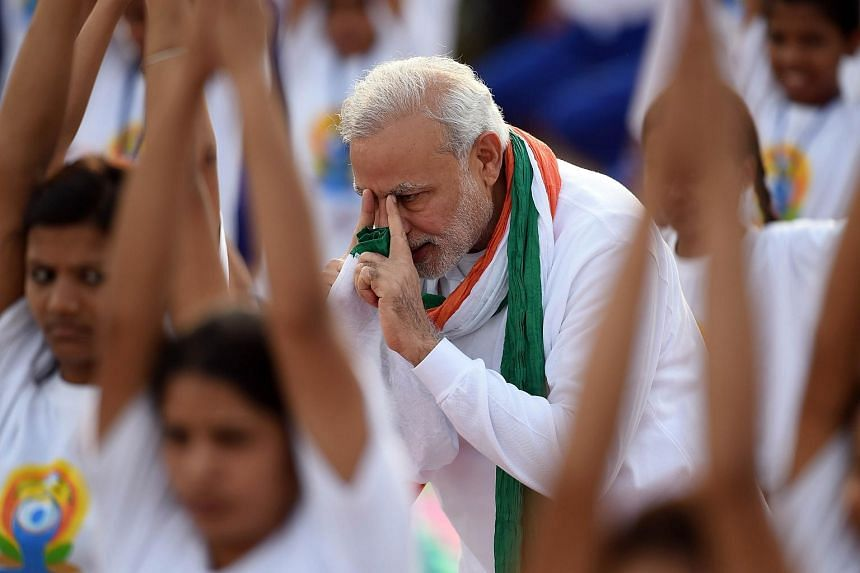 Indian Prime Minister Narendra Modi (centre) gives instructions as Indian yoga practitioners take part in a mass yoga session to mark the International Yoga Day on Rajpath in New Delhi on June 21, 2015.