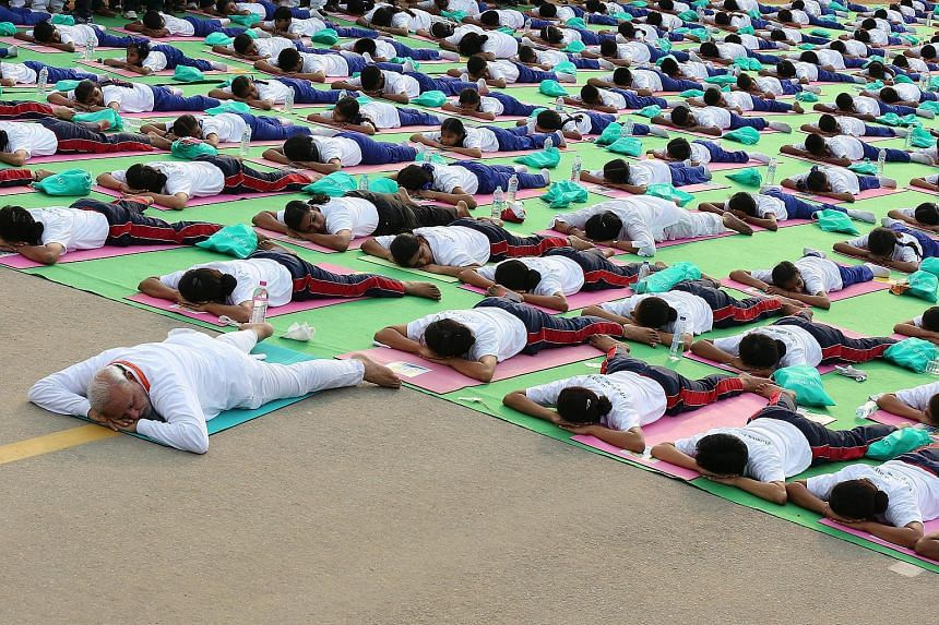 Indian prime minster Narendra Modi (front) performs yoga to mark the first international Day of Yoga at Rajpath in New Delhi, India, on June 21, 2015.