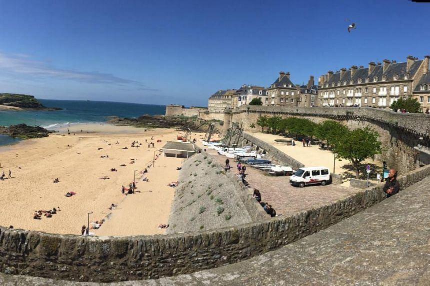 In the ancient walled city of St Malo, visitors can walk along the castle ramparts (above), visit the old town and have a French hamburger at Le Bistro de Jean restaurant.