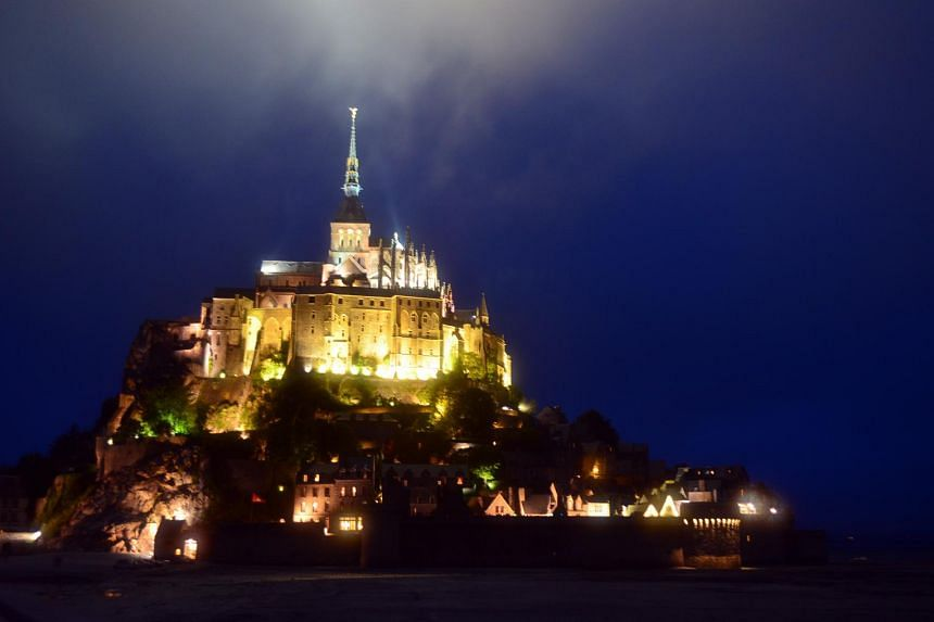 Mont St Michel in north-western France, famous for an abbey that sits atop it, is filled with daytrippers by day and transforms into a fairyland of lights by night (above).