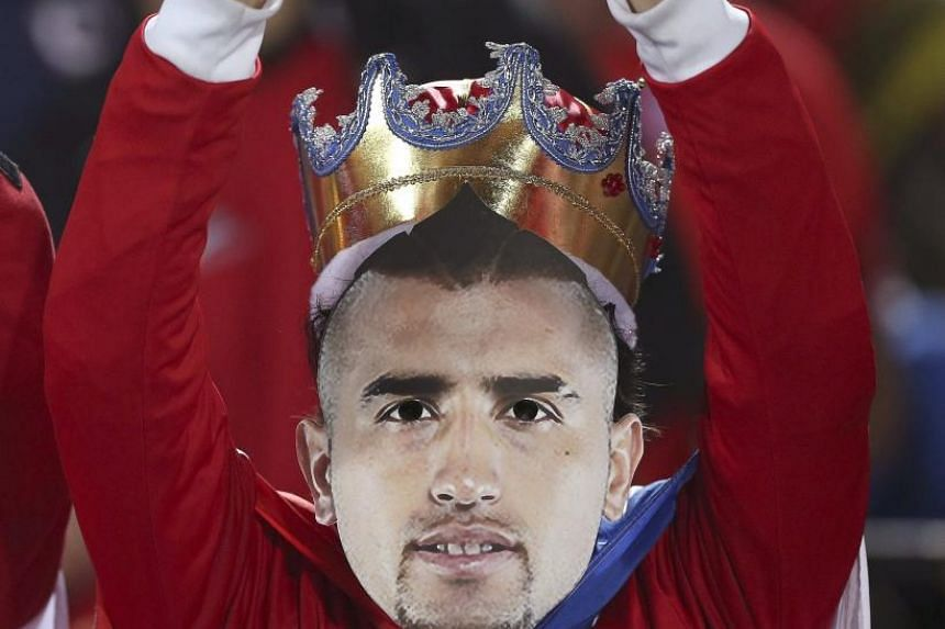 Chilean national team supporters wearing masks with the image of key player Arturo Vidal, backing him despite his four-month driving ban for driving while intoxicated