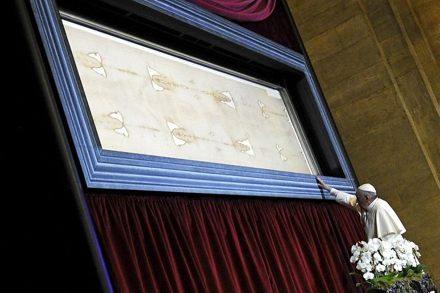 Pope Francis touches the Shroud of Turin during a two-day pastoral visit in Turin, Italy.