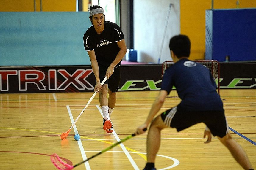 Singapore men's floorball player Akmal Shaharudin (left) playing in the ActiveSG Floorball 3v3 Event.