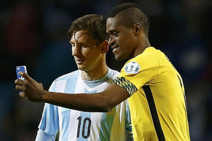 Jamaica forward DeShorn Brown (right) taking a selfie with superstar Lionel Messi, who earned his 100th Argentina cap, after his team had restricted the World Cup finalists to a 1-0 win in a Copa America Group B match. The invited Jamaicans impressed