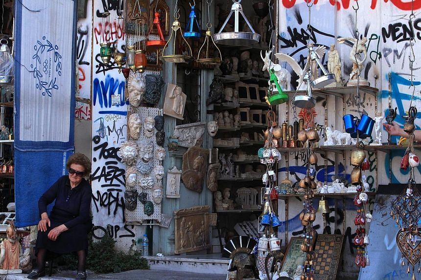 A shop owner waiting for customers outside her shop in the tourist area of Plaka in central Athens. Since December, Greeks have been hoarding cash, pulling more than €30 billion out of banks.