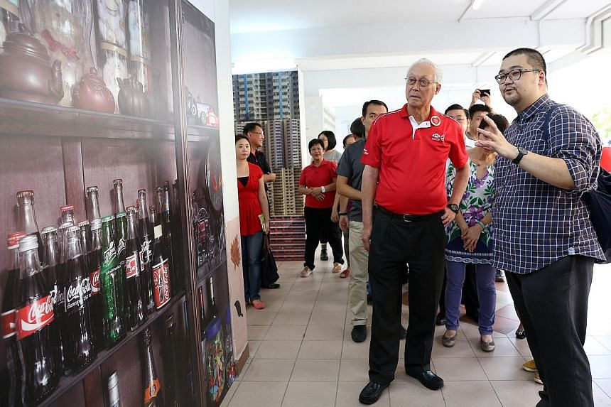 """Photographer Ang Song Nian explaining his photo series """"A Million Stories of Us"""" to ESM Goh Chok Tong."""
