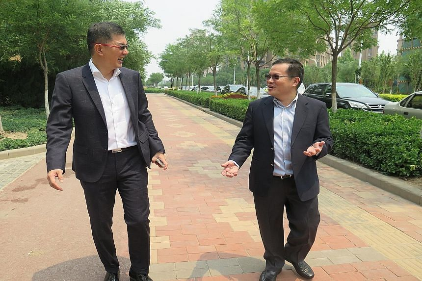 Tianjin Eco-city incoming head Liew Choon Boon (left) and outgoing chief executive Ho Tong Yen taking a stroll in the development, meant to be a model of sustainable growth for a rapidly urbanising China.