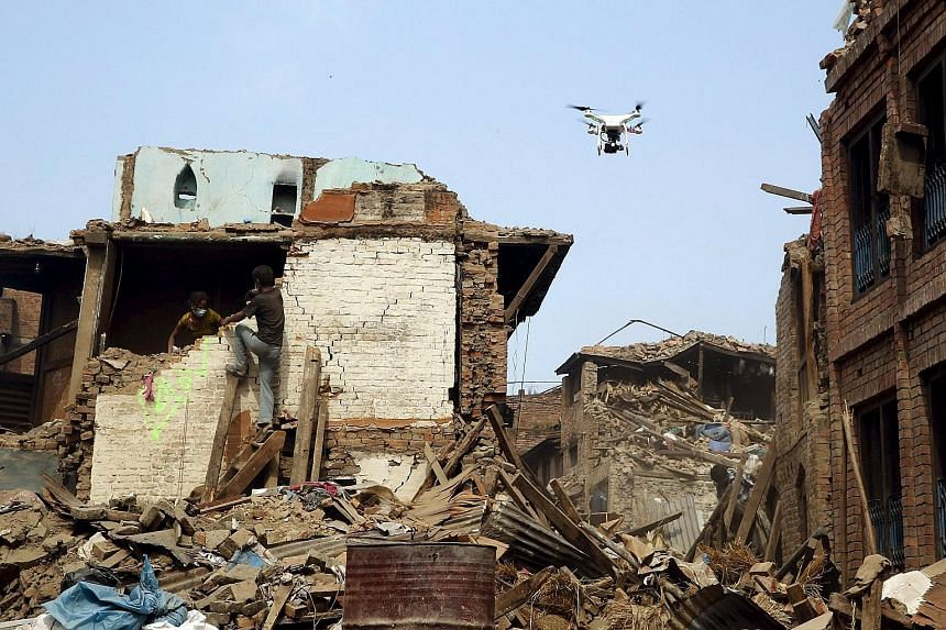 A drone flying over buildings destroyed by a 7.8-magnitude earthquake in Bhaktapur, Nepal, last month. Nepal was where an unprecedented number of drones were first used for humanitarian aid in a coordinated manner.