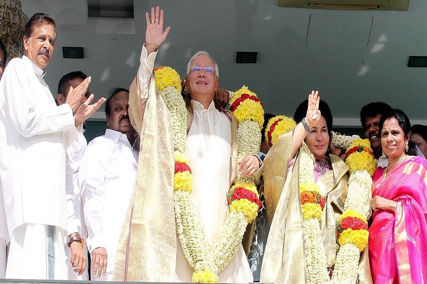 PM Najib and his wife Rosmah Mansor (with garlands) at a Thaipusam event earlier this year, along with Malaysian Indian Congress chief Palanivel Govindasamy (far left). While Mr Najib has faced increasing pressure from within his own party, Umno, he