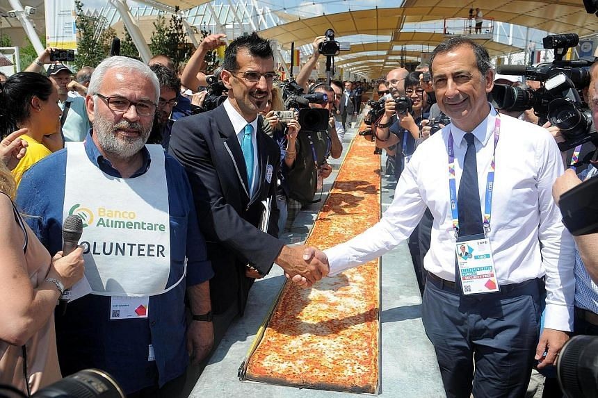 Guinness World Records judge Lorenzo Veltri (centre) congratulates expo commissioner Giuseppe Sala at Milan's 2015 Expo in Italy on Saturday. A total of 80 chefs from all over Italy took part in the creation of the world's longest pizza, snatching th