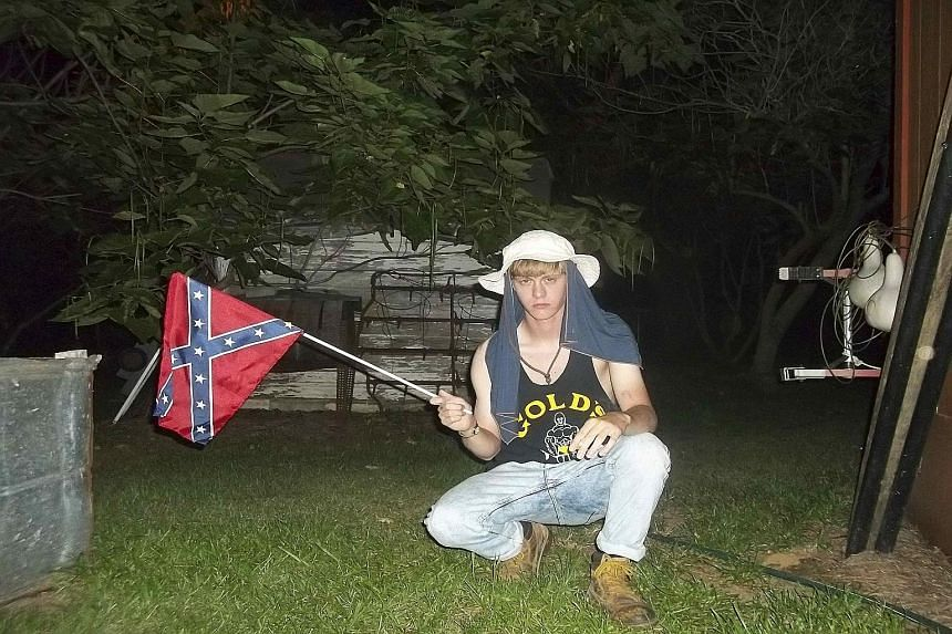 Dylann Roof was seen waving the Confederate battle flag (above) and burning the American flag on a website with a racist manifesto.